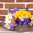 Beautiful flowers in crate on brick wall background — Stock Photo #49906621