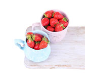 Ripe sweet strawberries in color mugs on cutting board isolated on white — Stockfoto