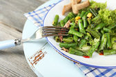 Salad with green beans, ham and  corn on plate, on color wooden background — Stockfoto