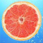 Fresh grapefruit in water — Stock Photo