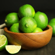 Fresh juicy limes in wooden bowl — Stock Photo #49953905