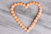 Heart of pills on wooden background — Stock Photo
