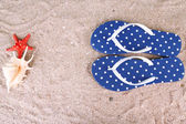 Color flip-flops on sand background — Stock Photo
