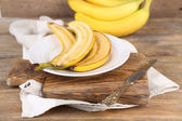 Halved and whole ripe bananas — Stock Photo