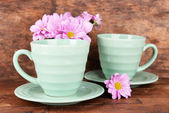 Cups and saucers with flowers — Stock Photo