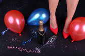Legs with confetti and champagne — Stock Photo