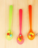 Plastic spoons with color pills on wooden background — Stock Photo