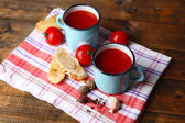 Homemade tomato juice in color mugs, toasts and fresh tomatoes on wooden background — Stock Photo