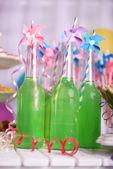 Flaschen trinken mit strohhalm auf dekorativen hintergrund — Stockfoto