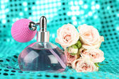 Perfume bottle with roses on fabric background — Stock Photo