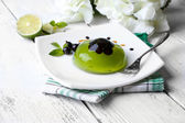 Green jelly with blackcurrant berries and sauce, on wooden background — Stockfoto