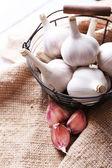 Fresh garlic in basket, on sackcloth background — Stockfoto