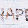 Word happy made from sea shells and stones on wooden background — Stock Photo #50271211