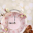 Beautiful vintage alarm clock with flowers on light background — Stock Photo #50271303