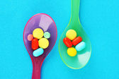 Plastic spoons with color pills — Stock Photo