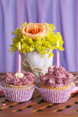Tasty cupcakes on table, on fabric background — Stock Photo