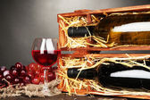 Wooden case with wine bottles, wineglass and grape on grey background — Stock Photo