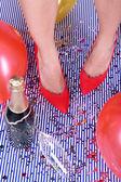 Beine mit Konfetti, Champagner und Luftballons auf dem Boden — Stockfoto