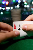 Chips and cards for poker in hands on green table — Stock Photo