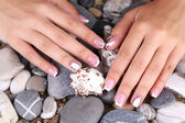 Female hand with stylish colorful nails on sea pebble background — Stock Photo
