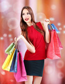 Beautiful young woman with gift bags on bright background — Stock Photo