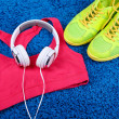 Sport clothes, shoes and headphones on color carpet background. — Stock Photo #50446759