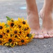 Rudbeckia flowers and female feet — Stock Photo #50447893