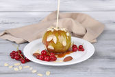 Caramel apple on stick with berries — Stock Photo