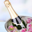 Frozen rose flowers in ice cubes and champagne bottle in bucket, on light background — Stock Photo #50451379