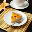Piece of homemade orange tart on plate, on color wooden background — Stock Photo #50543959