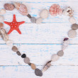 Heart made from sea shells and stones on wooden background — Stock Photo #50544305