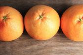 Ripe grapefruits on wooden background — Stock Photo