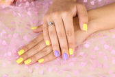 Female hand with stylish colorful nails, on color fabric background — Stock Photo