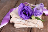 Old letters and flowers on wooden background close-up — Stockfoto