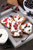 Bread with cottage cheese and berries on wooden tray close-up — Stock Photo