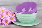 Bright bowls with flowers on wooden background — Stock Photo