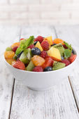 Delicious fruits salad in plate on table close-up — Stock Photo
