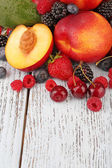 Peaches with berries on table — Stock Photo
