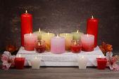 Schöne Kerzen mit Blumen auf Tisch mit braunen Hintergrund — Stockfoto