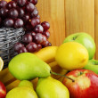 Composition of different fruits with basket on table on wooden background — Stock Photo #50799517