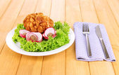 Chicken Kiev on croutons with lettuce salad, on wooden background — Stock Photo