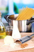 Process of preparing pasta. Composition with row spaghetti in pan, grater, cheese, on wooden table  on bright background — Stock Photo