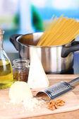 Proces van de voorbereiding van pasta. samenstelling met rij spaghetti in pan, rasp, kaas, op houten tafel op lichte achtergrond — Stockfoto