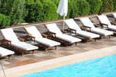 Sunbeds near swimming pool — Stockfoto