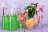 Bottles with drink and sweets — Stock Photo