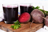 Glasses of fresh beet juice and vegetables on cutting board on wooden background — 图库照片
