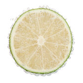 Fresh lime in water with bubbles — Stock Photo