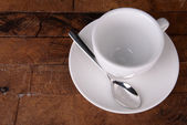 Empty cup with tea spoon on wooden background — Stock Photo
