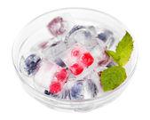 Cubes de glace avec des baies de forêt, dans le bol en verre, isolés sur blanc — Photo