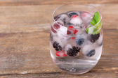 Cold cocktail with forest berries, frozen in ice cubes on wooden background — Foto Stock